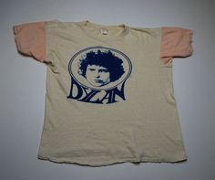 "There was a great Bob Dylan shirt sold in comic book ads and other magazines back in and around 1974 that portrayed Blonde on Blonde era Dylan but as some critic somewhere wrote, the illustration looked more like Mac Davis. It was a great T-Shirt though, lavender colored with ""Dylan"" written on it with groovy 1970s lettering.   I wonder if there's a shot of this online anywhere, since mine has no doubt turned to dust years ago... last I saw it my little brother wore it, 30 years ago oe so."