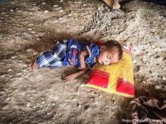 Syrian refugee child sleeping on dirt floor.