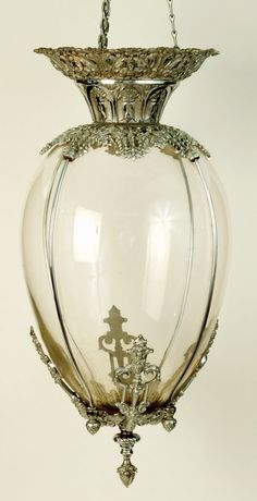 A pharmacy/drug store apothecary hanging show globe jar. Egg shaped glass jar encased in an ornately cast metal frame with silver finish. 19th century.