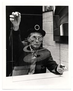 Marcel Duchamp looking through a part of the large glass.