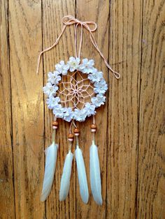 Handmade small dream catcher with light suede lace exterior covered in cream silk flowers with a peach interior. Clear beading accents with wooden beads