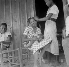 women sitting in chairs on a porch, one woman holding her baby while her hair is getting done, Earle, Arkansas, July 1936.