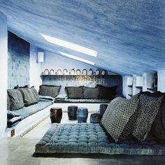 Salon aux murs et plafond en sous-pente peints avec un badigeon de chaux pour un effet bleu délavé. D'autres murs sont carrelés de zelliges bleu. Les canapés sont des matelas avec bouffettes recouverts de coussins habillés de tissu à motifs géométriques. Au fond, des têtes de bouddha sont alignée sur une corniche.
