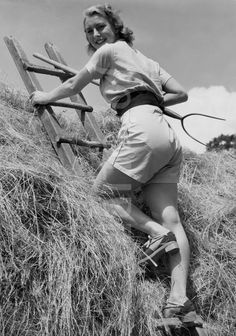 Land girl on hayrick, 1940s.