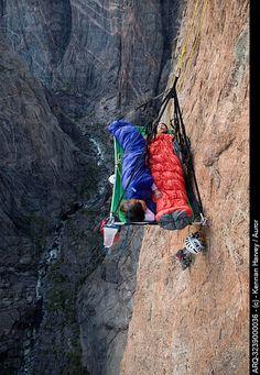 A man and woman sleep on portaledge while rock climbing a vertical face in Gunnison, Colorado.