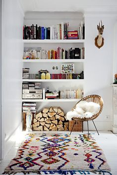 Niewielką wnękę można także wykorzystać do przechowywania książek i eksponowania pamiątek. Do tego wzorzysty dywan i wnętrze rodem ze skandynawii.