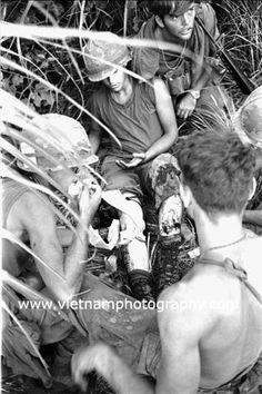 A medic treats a wounded soldier from Bravo Co., 4th Battalion, 31st Infantry Regiment, 196th Light Infantry Brigade, Americal Division. The man was hit during a firefight in the Hiep Duc Valley, 35 miles south of Danang. The valley was the site of some of the fiercest fighting of the war between Americans and North Vietnamese Army (NVA) regulars.