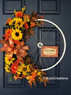 "Who doesn't remember the freedom you felt riding your bike? The scenery as it flew by, wind in your face? Going with the rustic Fall theme, this bike wheel wreath is perfect. Measuring 24-inches in diameter and a full 6-inches full, you find florals of yellow Sunflowers, Dogwood, Daisies, and yellow and orange Mums, creates on a bed of Fall colored greenery and ferns. The silver bike wheel sports it's own sign, ""Welcome Friends"" all topped off by a rustic bow of Fall plaids and prints of…"