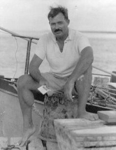 Ernest Hemingway sitting on a dock next to the Pilar, 1930s.