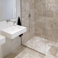 Smuk og elegant brusevæg uden synlige skruer og beslag samt brusebad med linieafløb, der matcher fliserne i resten af badeværelset. unidrain®: GlassLine & HighLine