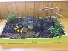 Pääsiäisen sanoma istutuksen muodossa. Näkkärilaatikko vuorataan, multaa ja kiviä sekä soraa, oksia ja varpuja maisemointiin. Springlespurkki tai muu putkilo mullan alle haudan suuaukoksi, kivi eteen.  Rairuohon siemeniä joka puolelle maastoa, nyt tämä jo vihertää.