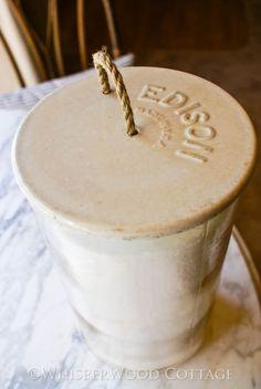 Vintage battery jar repurposed as toilet paper holder.