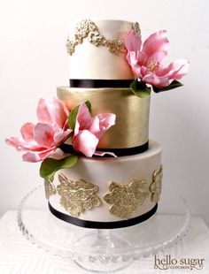 Three-tiered white, gold, and black wedding cake with pink flowers.