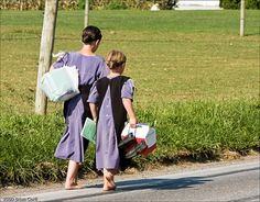 """Amish Sisters, Barefoot, Lancaster County, Pennsylvania  Two young Amish sisters are on their way home from school, one carrying her books in a grocery store """"book bag"""" and the other carrying her shoes and lunchbox. Nothing like wiggling those toes after a long day in school !"""