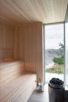 A lovely stepped sauna made for three or four people to sweat. Has a floor to ceiling window looking out on water. This natural sauna looks like it's made of cedar.