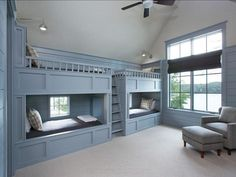 Wall of built-in bunk beds. Love that they have windows in them!