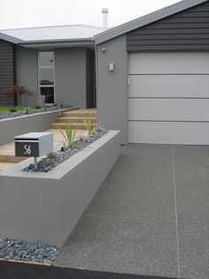 Exposed coloured concrete driveway, with trowel finished path beside - more at…