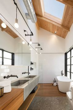 High ceiling bathroom, well lit, polished aggregate flooring mixed with slatted timber, timber and cement vanity and long mirror for depth. Black framed windows and deep bath with open shower.