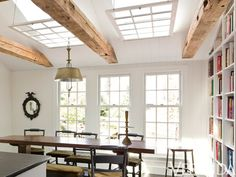 When a homeowner wanted to maintain his sun-drenched kitchen—yet disliked the 1980s-style skylights—Carter sought ways to make them complement the home's original architecture. His solution: hanging mullioned windows from chains under the recesses. They echo the look of the nearby windows, while masking the modern, plate-glass skylights. Plus, suspending them parallel to the floor and beams, they visually level the pitched ceiling, another '80s vestige.   - Veranda.com