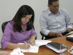 Patricia Mayorga, executive director of FUNDEMOS Group, signs the grant under which the nonprofit will produce radio plays encouraging effective citizen participation in politics.