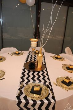 Black and Gold Table Setting and centerpiece. Black and white chevron runner. Gold spray painted bottles. Gold gift boxes. Gold looking plastic forks. Gold chargers. Birthday or Wedding decor.