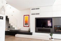 Wyróżniająca się strefa kominkowo-telewizyjna łączy się z czarnym początkiem schodów.