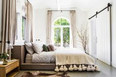 bright and neutral bedroom with eclectic lamp, gray and tan a fur throw