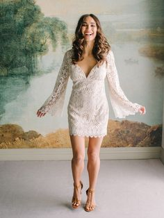 Indie Lace Mini Dress | Desert reveries and an untamed spirit, Indie oozes effortless bohemian vibes. Featuring long lace bell sleeves, a plunging neckline, and a low open back with jeweled silk tassel ties, this crochet lace mini is perfect for a beach wedding, or a dance-the-night-away party.