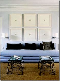 A collection of intaglios framed & displayed over modern, blue velvet couch.
