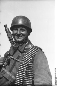Smiling German paratrooper carryng an MG and ammos.  Russia 1943.