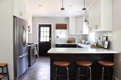 Black and white Ikea kitchen reveal: black lower cabinets, white upper cabinets, Corian countertops, subway tile backsplash, herringbone tile floor