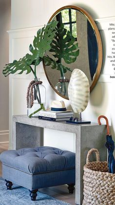 Home decorating ideas - Console table styling at entry.  Skinny silver table with tufted ottoman, round mirror and woven umbrella basket.  Simple, classy and functional.