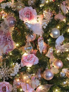 Beautiful shabby Victorian Christmas tree, decorated with pink roses, glass and crystal ornaments, and bunches of pearls.