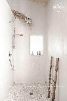 Een kiezelmozaïek op de vloer combineert altijd mooi met een verder witte badkamer. Door in deze badkamer stoere, houten kastjes en dergelijke te plaatsen ontstaan accenten.