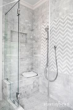 White and gray tile shower. Herringbone pattern.
