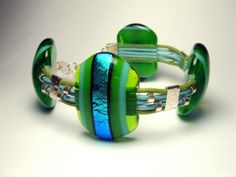 Designer Bracelet.  Brighten up your outfit with this green and blue bracelet consisting of 4 fused glass stones connected with silk cord and sterling silver spacers. This striking bracelet was created by jewellery designer Jana Sobelmann of JanArt.