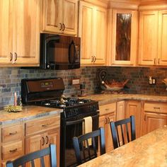Nice bright kitchen. Light woods are contrasted well with the dark appliances and walls.