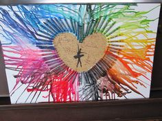 Crayon art with modge podged scrap book paper and then a cut out silhouette again modge podged over the top.