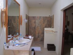 This is the bathroom at Sumilon Island Resort. We like the open shower. It's laid out in a linear fashion, long and narrow. Behind me and to the right is the toilet, separated by a half wall similar to the half wall for the shower. I know we talked about enclosing the toilet in its own room but this layout here will work great.
