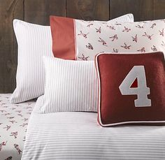 Bedding in navy stripe.  At least one red number pillow on each bed.