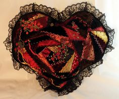 "Crazy Quilt Heart Pillow, with variations of red, gold, and black patterns, a girl and heart pendant on front, button adornments, lace, and embroidered flowers. Approximately 10"" x 12"".  ~By FolkloreTreasures on Etsy"