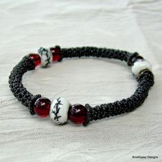 """An original design by KnotGypsy - Simply classic fun!  Bracelet is hand knotted with nylon    cord in black and beaded with lots of tiny seed beads in black.  Lovely ceramic *Dionne black & white focal beads surrounded by garnet red glass rounds.  Bracelet is between medium and large - inner circumference is about 8 1/2 inches.  I    design my jewelry to be durable as well as beautiful.  One of the    things I love about beaded micro macrame jewelry is that it feels so    """"friendly"""" in the …"""
