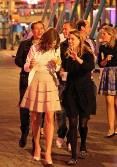 (R) Princess Beatrice is seen sharing a moment with bride-to-be Lizzy  Wilson (L) on May 1st and both women are holding cups presumably filled with alcoholic beverages.