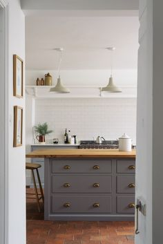 A white metro tiled splashback, simple pendant lights, quarry tiled floor and a Shaker kitchen island painted in deVOL's 'Lead' colour