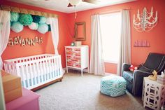 Vintage Modern Coral Nursery with  pompoms over the crib - #projectnursery #nurserydesign #coral