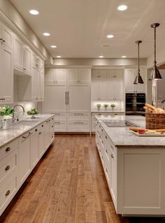 A long kitchen with a large center island, gunmetal pendant lights, and kashmir white granite counters.