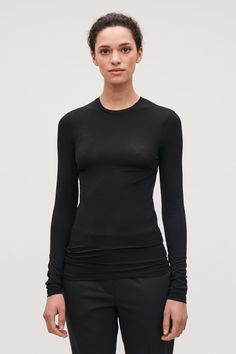 Designed to sit close to the body, this long-sleeved top is made from a light, stretchy fabric with a soft jersey quality. An essential style, it is completed with a round neck and neat double topstitching at the edges. Wardrobe Sale, Small Wardrobe, Tailored Trousers, Trousers Women, White Shirts, Dresses For Sale, New Dress, Black Tops, Long Sleeve Tops