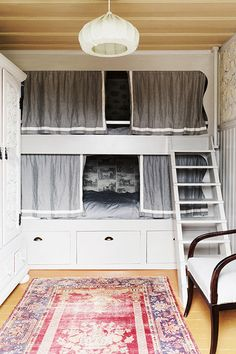 A Nostalgic Summer Sanctuary in Sweden: A hanging lantern and an antique area rug make a multifunctional space feel expansive. The bunks house full-size mattresses, enabling the room to accommodate summer visitors.