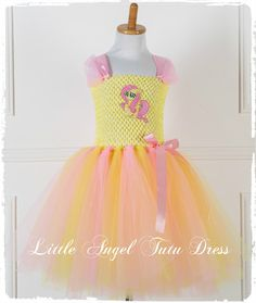 MLP Fluttershy Fancy Dress Costume - Inspired by My little Pony !!! This is the perfect dress for your little princess who loves My Little Pony. Here I have created a tutu dress which was inspired by the Fluttershy pony. The bodice is made with yellow tutu top and is fully lined (pictures show dress without lining), where I have added layers and layers of baby pink and yellow tulle to the for the skirt. I have then added pink satin and tulle straps. I have also attached a Fluttershy…