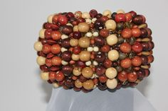 """Miss Basket Bangle Beaded bangle Fits up to 7 ½"""" How to determine if it will fit: (Fold your thumb over your palm, measure from the top thumb knuckle around the top pinky knuckle back to the top thumb knuckle) Beads: wood, glass, ceramic, seed Colors: brown, tan, red, cream Height: 3""""  width: 14"""" $60"""